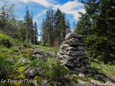 Un cairn et la trouée par laquelle passe la limite sur le Vercors.